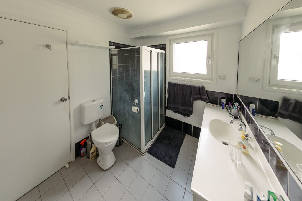 A wide-angle view of a bathroom, the floor tiles are sickly grey and the grout looks dark just from being dirty. A cheap-looking white vanity with a single sink is in the right of the photo, the shower screen around the shower is in the middle and is totally soap scum-encrusted. The tiles in the shower are black with discoloured grout between them. A toilet roll holder is attached by suction cup to the outside of the shower screen next to the toilet, the toilet itself is small and very plastic-looking and sits next to the shower. In the ceiling above the shower is an EXTREMELY yellowed plastic fan vent.