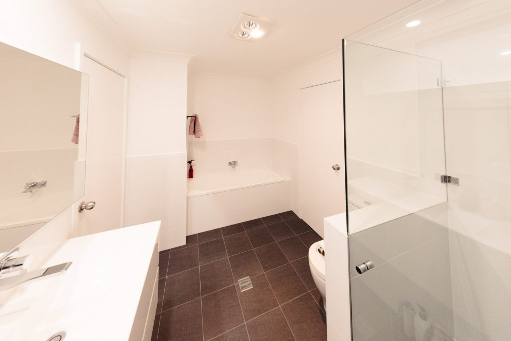 The fantastic new bathroom, a white wall-hung double-basin vanity and wall-mounted chrome taps are at the left of the photo. In the centre is the bath surrounded by white wall tiles, at the right is a waist-high thin wall tiled in white, and that side of the shower screen starts at the top of the wall. The wall tiles are white and the floor tiles are a dark slate grey.  A dark pink towel hangs on the wall over the left end of the bath.