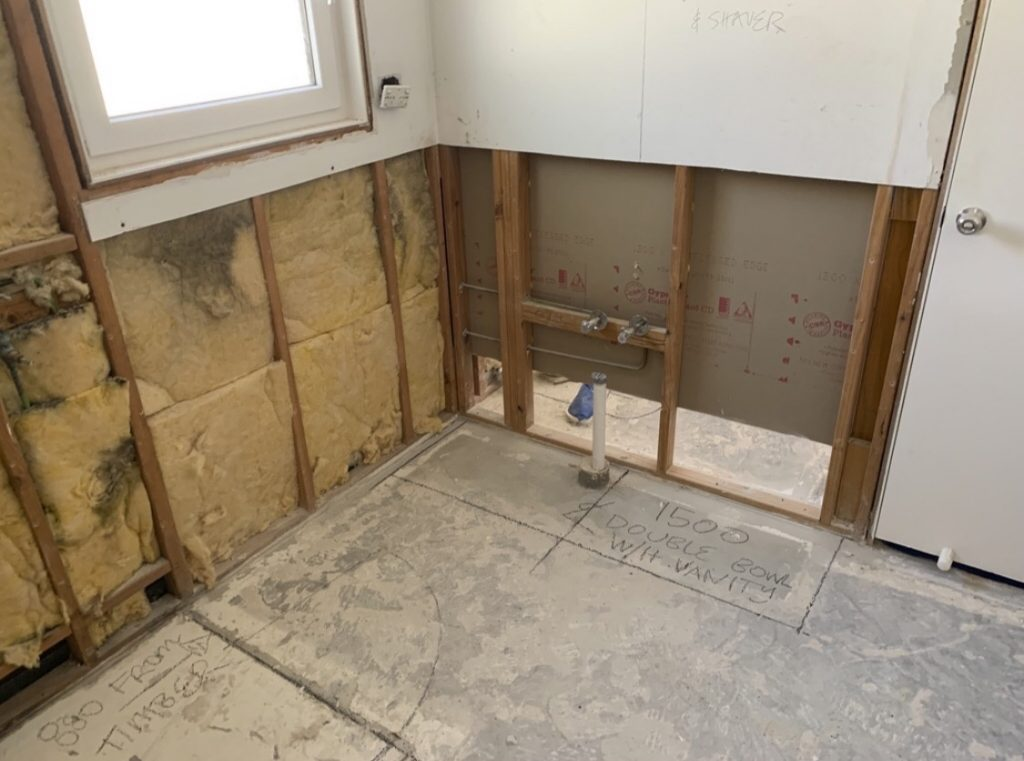 The bathroom with no tiles or gyprock on the bottom half of the walls, just bare timber frame and insulation.