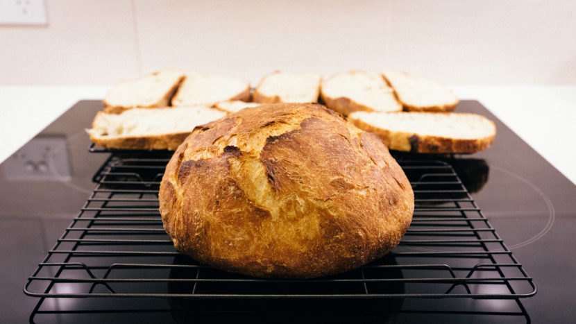 A round, brown, very crusty loaf of bread sitting on a cooling rack, with sliced up pieces from another loaf behind it