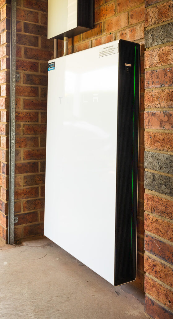 A side-on view of a white Tesla Powerwall 2 battery mounted against a red brick wall.