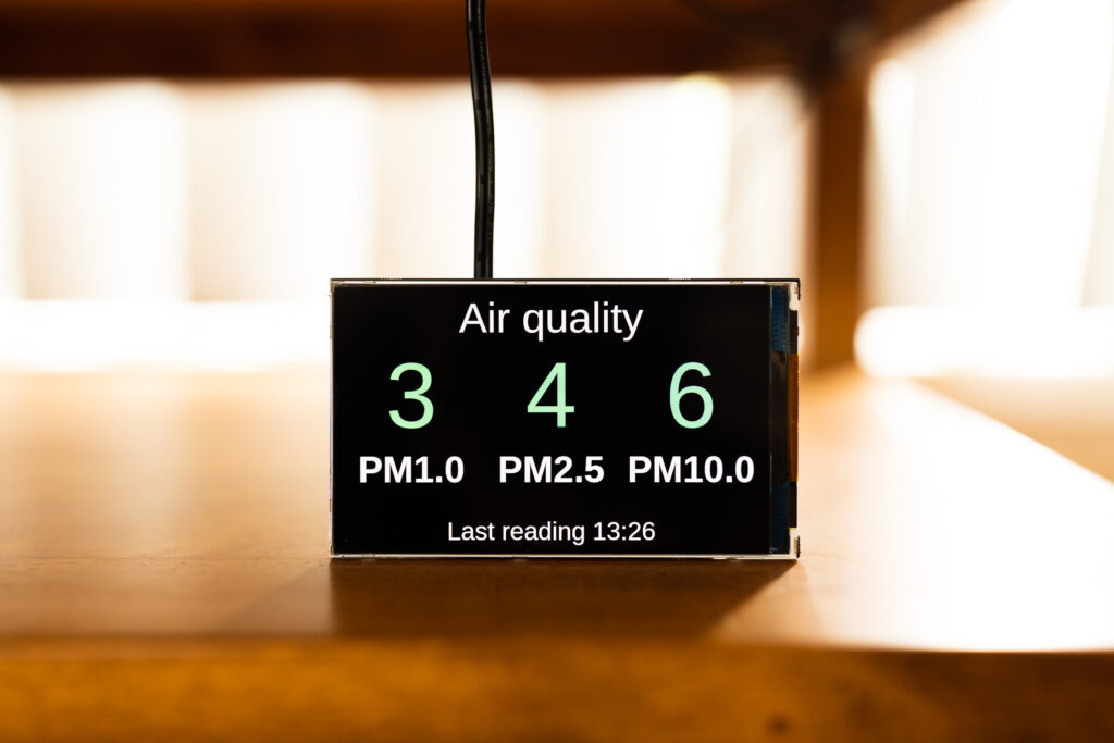 "A small 4"" LCD display showing the air quality values for PM1.0, PM2.5, and PM10."